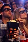 3D movie and popcorn. Young couple eating popcorn in multiplex movie theater, watching 3D movie. Focus on popcorn Royalty Free Stock Photography