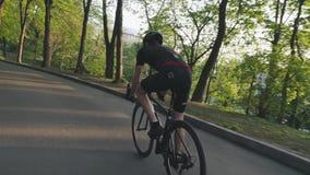 D?nner athletischer Radfahrer, der auf Rennrad im Park absteigt Radfahrer, der die schwarze Ausstattung f?hrt schwarzes Fahrrad t stock video