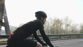 D?nner geeigneter Radfahrer, der Fahrrad unter die Br?cke f?hrt R?ckseite folgen Schuss des radelnden Fahrrades des Fahrradreiter stock video