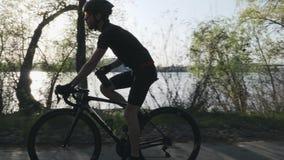 D?nnes triathlete auf Trinkwasser des Fahrrades Sun-Glanz durch B?ume Durstiges triathlete trinkt Wasser w?hrend des Trainings tr stock footage