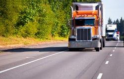 D'orange remorque classique de cargueur de camion semi sur le chemin élevé Image stock