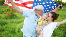 D?a patri?tico Comida campestre americana preciosa de la familia el 4 de julio Juegos de abuelo con el nieto El bebé se está sent almacen de metraje de vídeo