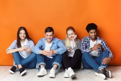 D?pendance d'instrument Adolescents avec des smartphones, mur orange image libre de droits