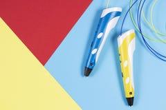 3d pennen met kleurrijke plastic gloeidraad op blauwe achtergrond Stock Foto's