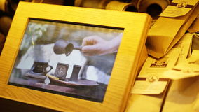 3D picture in a wooden frame illustrating hands of a woman serving a cup of coffee with respect of old tradition of stock footage