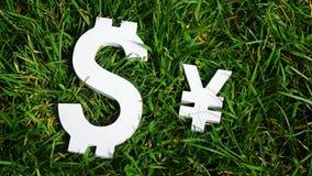 3d pojęcia dolarowej wymiany spadać stopień wzrostu Jen i dolarowy znak na trawie Fotografia Royalty Free