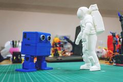 3D printed astronaut, cosmonaut and cute robot on the background of devices and laptop. Kropivnitskiy, Ukraine – 12 may, 2018: 3D printed royalty free stock photography