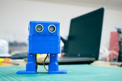 3D printed Funny blue robot on the background of devices and laptop. Robot model printed on automatic three dimensional 3d stock images