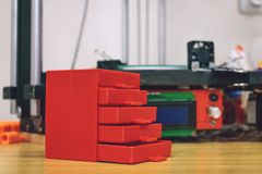 3D printed red plastic dresser on the background of three dimensional 3d printer. furniture model printed on automatic three. Dimensional 3d printer, printing stock photo