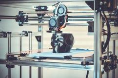 3D printer die een model in de vorm van zwart schedelclose-up drukken Stock Foto