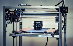 3D printer die een model in de vorm van zwart schedelclose-up drukken Stock Afbeeldingen