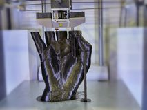 3D printer head moving to generate a black uman hand stock photography