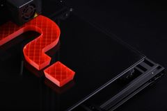 A 3D-printer manufacturing a big question mark from red plastic in dark surrounding with classy light mood. Oblique top view on 3D-printer with big question royalty free stock image