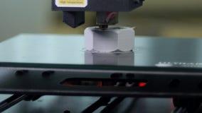 3D printer printing a gray screw. Detail shots of a 3d printer printing a big gray screw stock footage