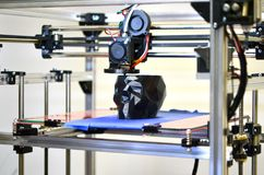 3D printer printing a model in the form of black skull close-up. The 4ht industrial revolution. Automatic three dimensional performs plastic modeling stock images