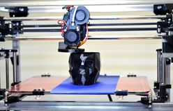 3D printer printing a model in the form of black skull close-up. The 4ht industrial revolution. Automatic three dimensional performs plastic modeling stock photography