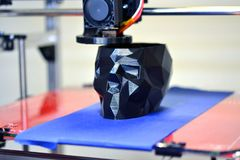 3D printer printing a model in the form of black skull close-up. The 4ht industrial revolution. Automatic three dimensional performs plastic modeling royalty free stock photo