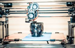 3D printer printing a model in the form of black skull close-up. The 4ht industrial revolution. Automatic three dimensional performs plastic modeling royalty free stock images