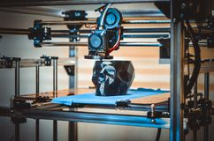 3D printer printing a model in the form of black skull close-up. The 4ht industrial revolution. Automatic three dimensional performs plastic modeling stock photos