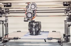 3D printer printing a model in the form of black skull close-up. The 4ht industrial revolution. Automatic three dimensional performs plastic modeling stock photo
