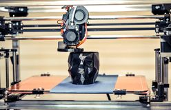 3D printer printing a model in the form of black skull close-up. The 4ht industrial revolution. Automatic three dimensional performs plastic modeling royalty free stock image