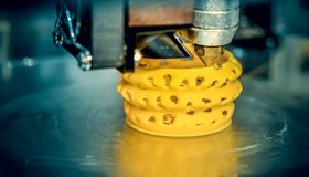 3d printer printing objects yellow form closeup. Royalty Free Stock Images