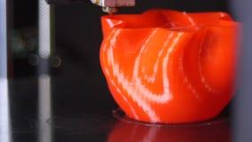 3D printer printing a red vase, Black background. A 3D printer printing a red vase with black background stock footage