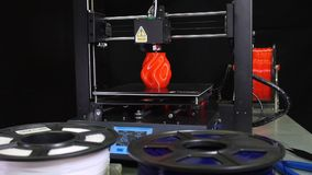 3D printer printing a red vase, Black background. Camera movement of a 3d printer printing a red vase  in front of black background stock footage