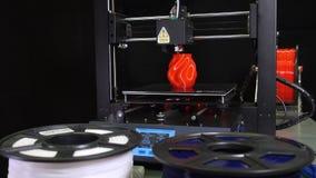 3D printer printing a red vase, Black background. Camera movement of a 3d printer printing a red vase  in front of black background stock video footage