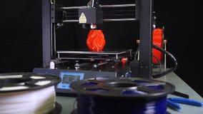 3D printer printing a red vase, black background. Camera movement of a 3d printer printing a red vase  in front of black background stock video