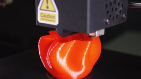 3D printer printing a red vase, Black background. A 3d printer printing a red vase  in front of black background stock video footage