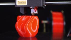 3D printer printing a red vase, Black background. A 3d printer printing a red vase  in front of black background stock video