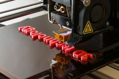 3D printer printing words with red plastic. 3D printer printing the words `3D technology` with red plastic, close up with print head visible Stock Photography