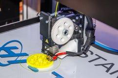 3D printer prints plastic piece gear Stock Images