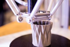 3d printer in the process of making a geometric vase. 3d printer stock photo