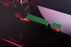 A 3D-printer producing an exclamation mark sculpture from green plastic in pink neon light to express technology opportunity. 3D-printer producing big royalty free stock photo