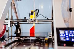 3d printer printing red plastic component stock images