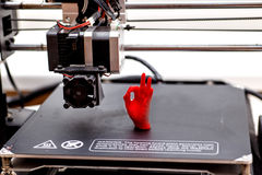 3d printing machine and printed item. printed palm red. 3d printing machine and printed item stock photo