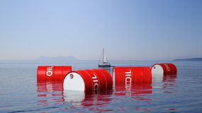 3D red oil drums floating on sea surface. With blue sky and sailing boat in background Royalty Free Stock Images