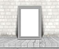 3D blank silver picture frame on a wooden table leaning against. 3D render of a blank silver picture frame on a wooden table leaning against a brick wall Stock Image