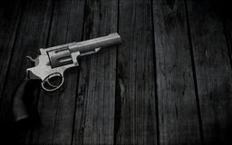 3D handgun on a grunge wooden texture. 3D render of a handgun on a grunge wooden texture Stock Photography