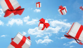 3d render of many white gift boxes with red bows falling from the sky in the clouds. Unexpected fortune. Promotions and special offers. Shopping and sales Royalty Free Stock Images