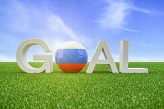 3d render - The text Goal on a green field and in the background. A blue sky. The zero is represented by a football in the typical national colours of the Stock Photos