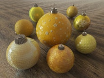 3D render of yellow and gold holiday decoration baubles on wooden surface Royalty Free Stock Images