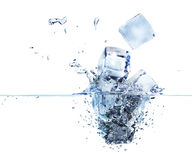 3d rendered ice cubes splashing into water. Four ice cubes splashing into water with bubbles and drops visible. Illustratively rendered in 3d Stock Photo