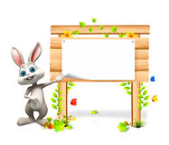 Bunny stands near wooden sign Stock Image