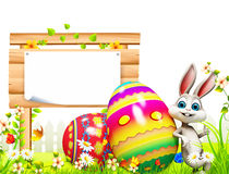 Easter bunny with big wooden sign and eggs Stock Image