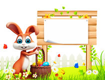 Easter bunny with big wooden sign and eggs basket Stock Photography