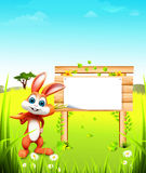Easter bunny with carrot and sign on green grass. 3d rendered illustration of  easter bunny with carrot and sign on green grass Royalty Free Stock Photography