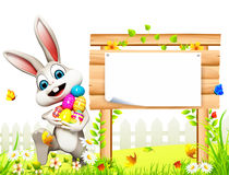 Gray easter bunny playing with eggs near wooden sign Royalty Free Stock Photography